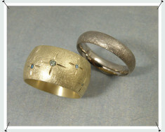Geelgouden spitsovale trouwring met groene diamant. Spitsovale witgouden trouwring.
