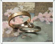 Trouwringen, witgouden ring met diamant en roodgouden structuur ring.